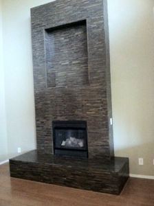 Mosaic strip glass installed on fireplace to create a beautiful center piece in the living room of this home.